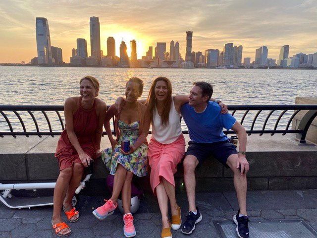 Courtney and friends sitting in front of the Hudson River and Jersey City, New Jersey